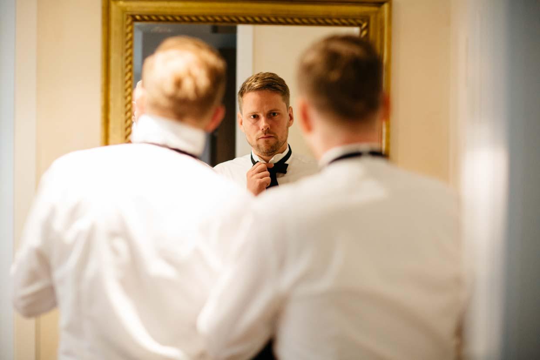 Bräutigam und Trauzeuge stehen vor einem Spiegel und binden gemeinsam ihre Fliegen