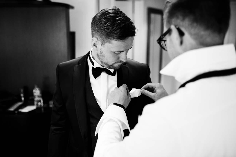 Trauzeuge richtet das Einstecktuch des Bräutigams zurecht