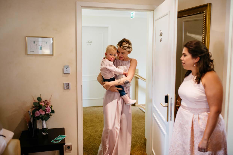 Brautschwester kommt mit Kind zur Tür herein