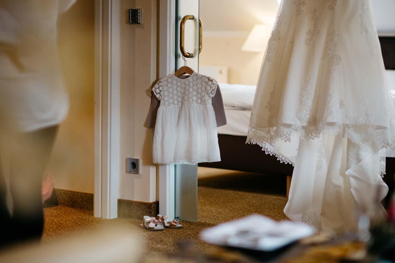 Kleid des Kindes hängt neben dem Brautkleid