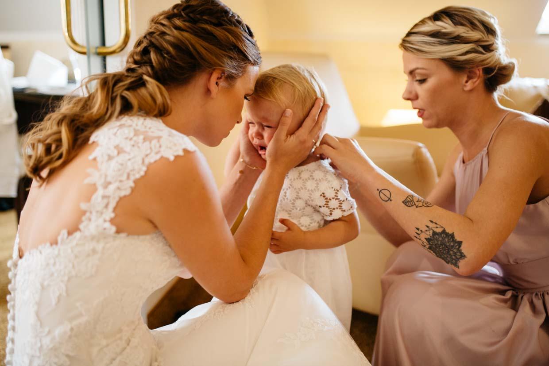 Kind weint beim Anziehen des Kleidchens