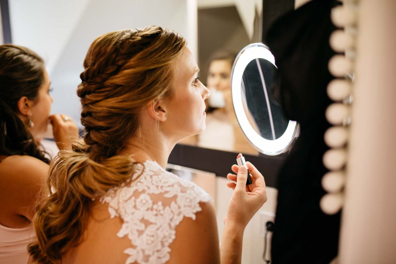 Braut schminkt sich die Lippen vor einem Vergrößerungsspiegel