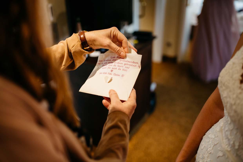 Brautmutter zieht Geschenk aus einem Umschlag