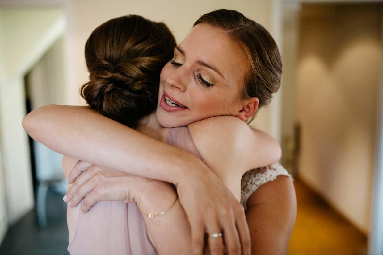 Braut umarmt Trauzeugin und ist emotional ergriffen