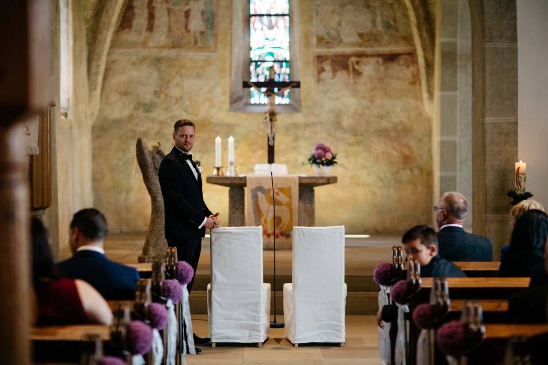 Bräutigam wartet am Alter auf die Braut