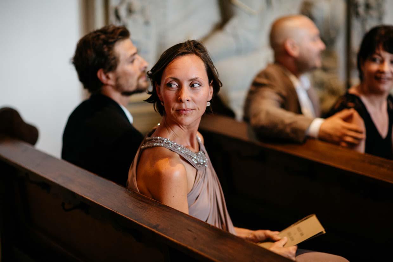 Hochzeitsgäste sitzen in der Kirche und schauen nach hinten