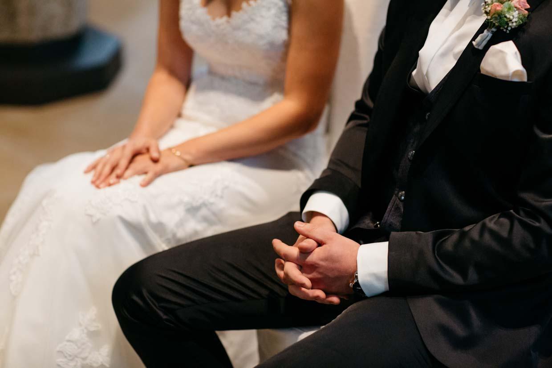 Hände des Brautpaares während des Gottesdienstes fotografiert