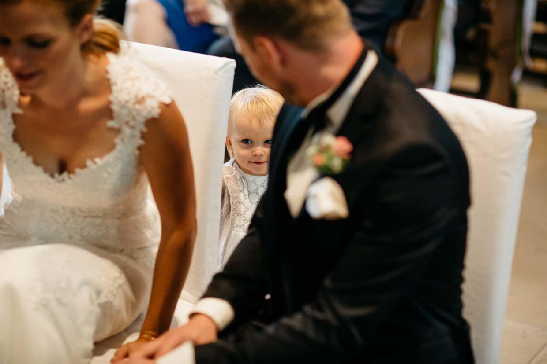Kind des Brautpaares schaut zwischen den Stühlen hervor