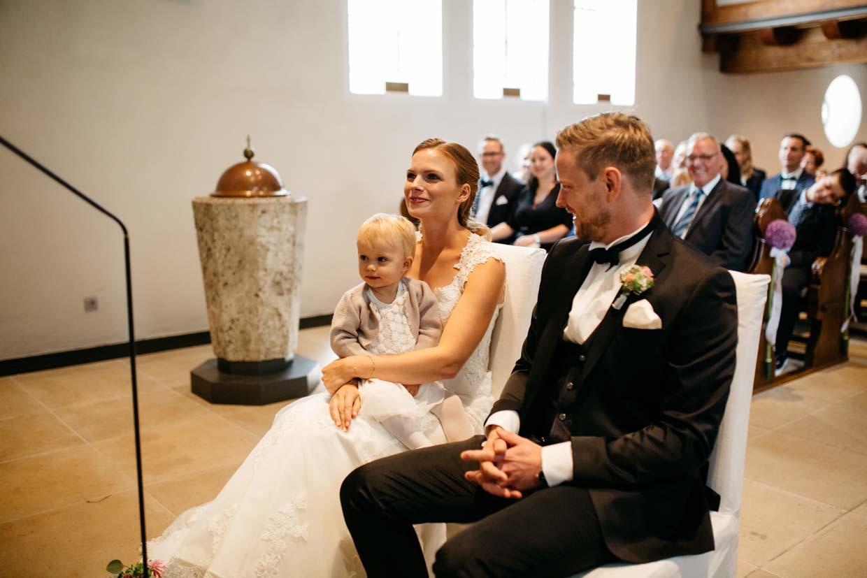 Kind sitzt auf dem Schoß der Braut während des Gottetdienstes