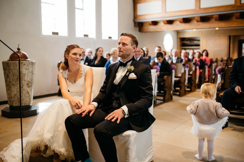 Brautpaar sitzt vorne in der Kirche und Kind spielt im Hintergrund mit ihrem Kleidchen