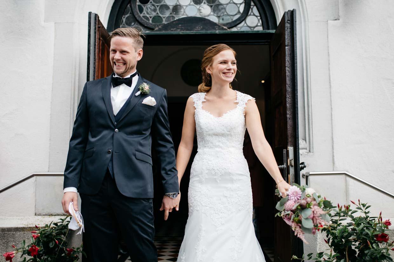 Brautpaar steht draußen vor der Kirche und freut sich