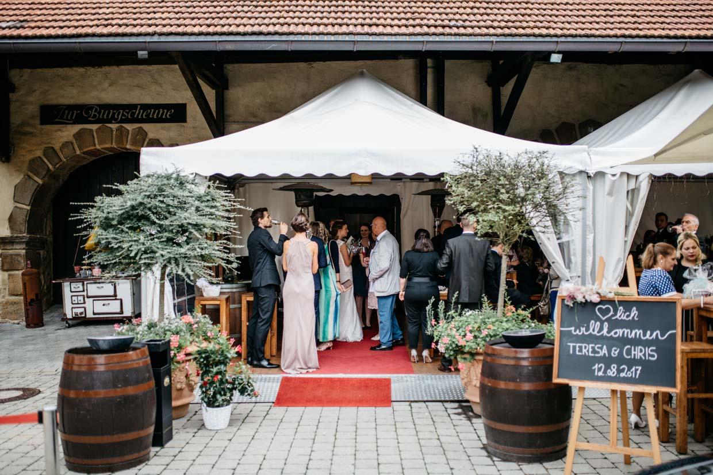Hochzeitsgäste stehen im Zelt beim Sektempfang