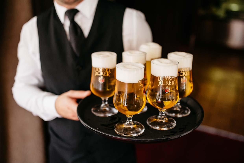 Kellner trägt ein Tablett mit vollen Biergläsern