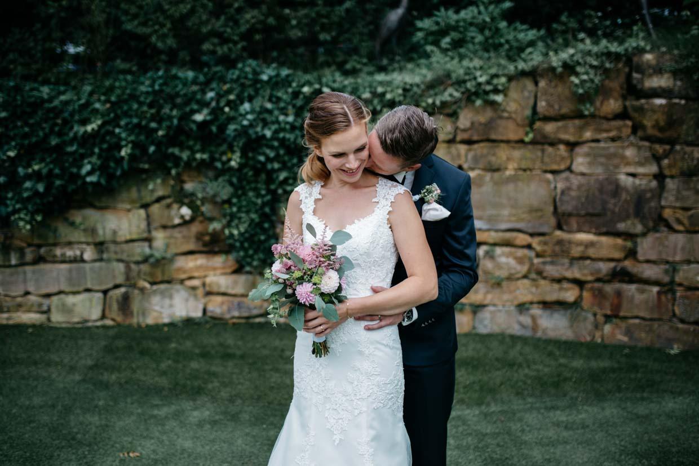 Bräutigam steht hinter der Braut beim Brautpaarshooting