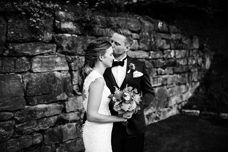 Bräutigam küsst die Braut auf die Stirn beim Brautpaarshooting