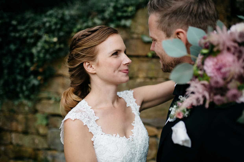 Braut hält den Brautstrauß über die Schulter des Bräutigams und schaut ihn liebevoll an