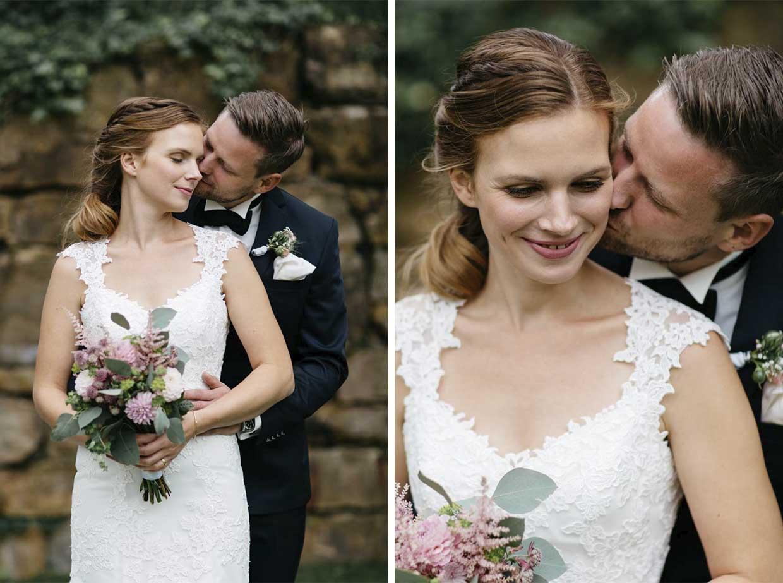 Bräutigam steht hinter der Braut und küsst sie sinnlich auf die Wange