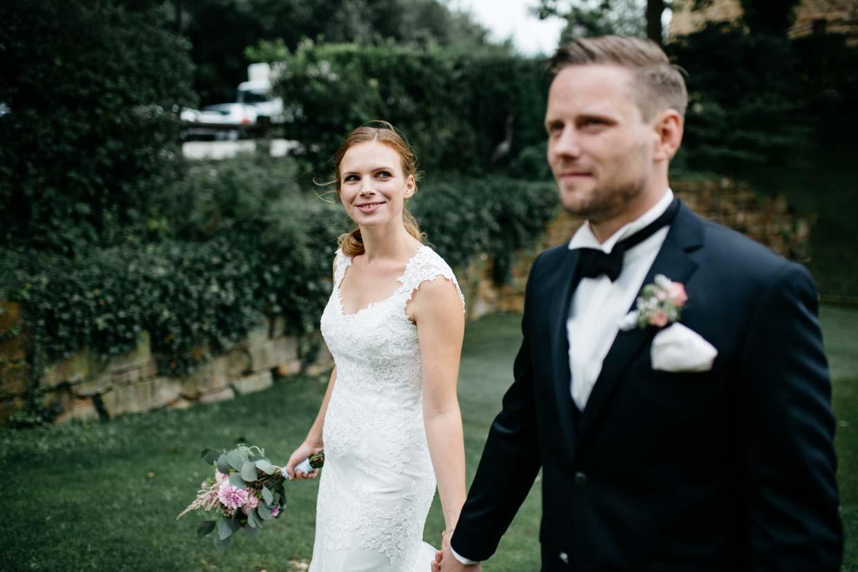 Brautpaar hält Händchen und geht spazieren