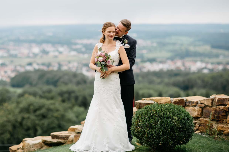 Bräutigam steht hinter der Braut und flüstert ihr ins Ohr