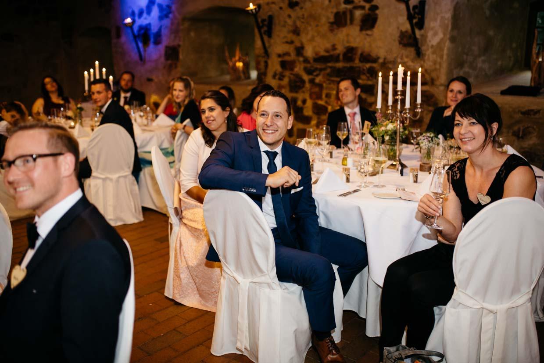 Hochzeitsgäste sitzten an runden Tischen und hören dem Bräutigam zu