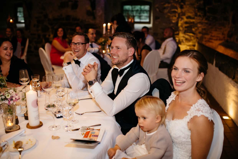 Brautpaar lacht und hört einer Rede zu