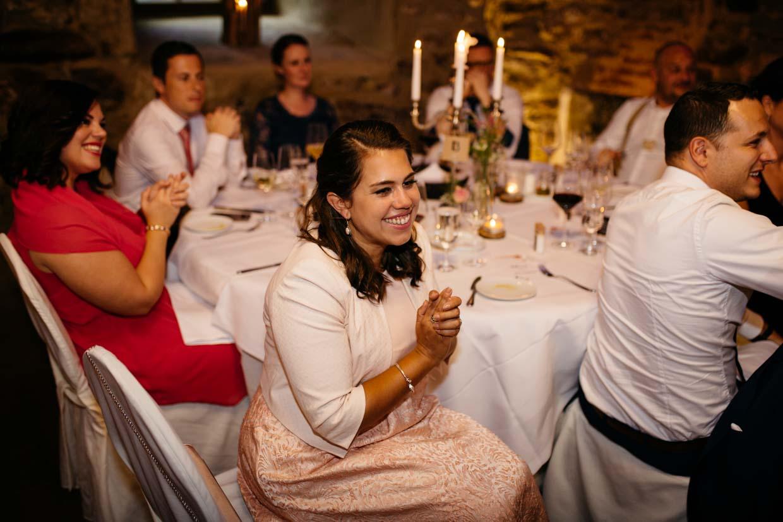 Hochzeitsgäste sitzten am Tisch und freuen sich