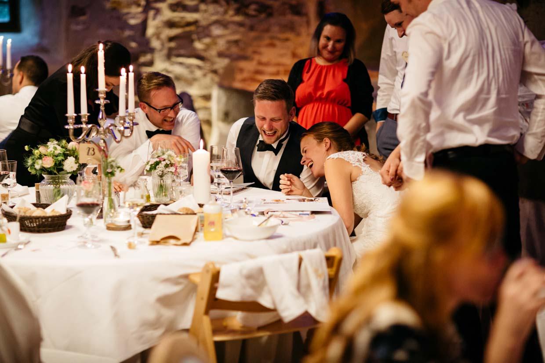 Brautpaar lacht ausgelassen am Tisch mit Hochzeitsgästen