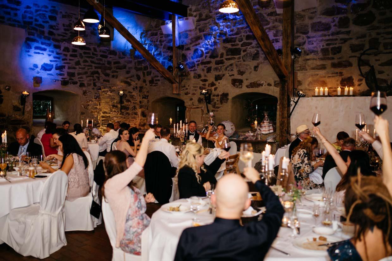 Hochzeitsgesellschaft hält die Gläser hoch und stoßt gemeinsam an