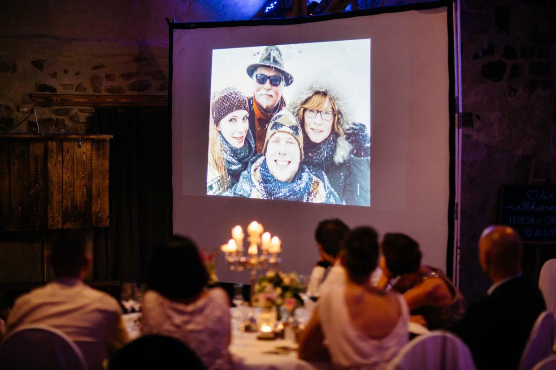 Brautpaar ist mit Eltern auf einem Foto bei der Beamershow zu sehen
