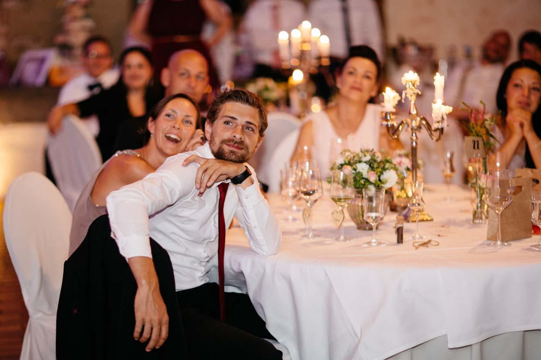 Hochzeitsgäste schauen sich eine Beamershow an