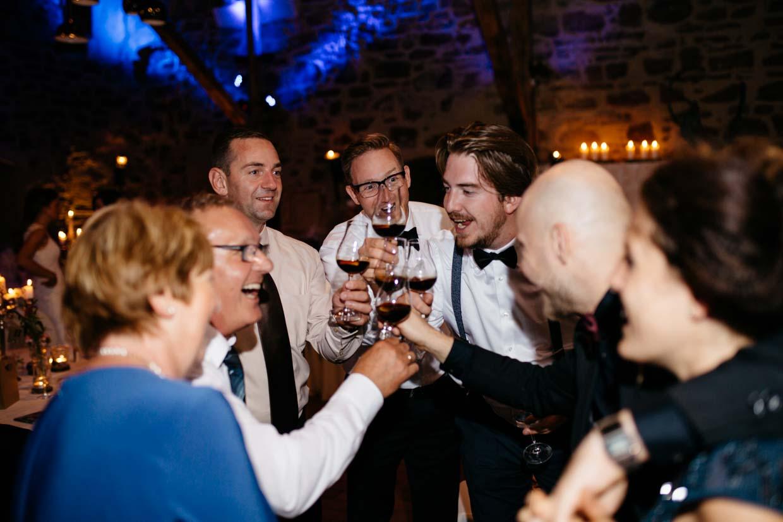 Hochzeitsgäste stehen im Kreis und stoßen gemeinsam an