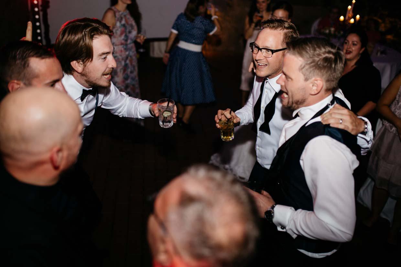 Hochzeitsgäste und Bräutigam beim Feiern