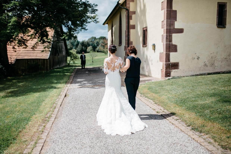 Braut mit Trauzeugin auf dem Weg in die Kirche