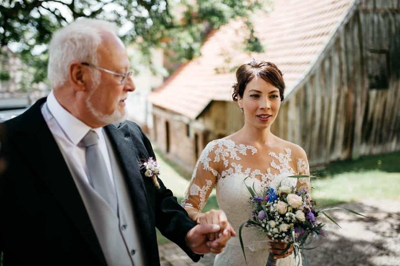 Brautvater mit Braut vor der Kirche