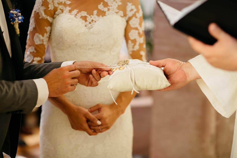 Bräutigam entnimmt Ring vom Ringkissen