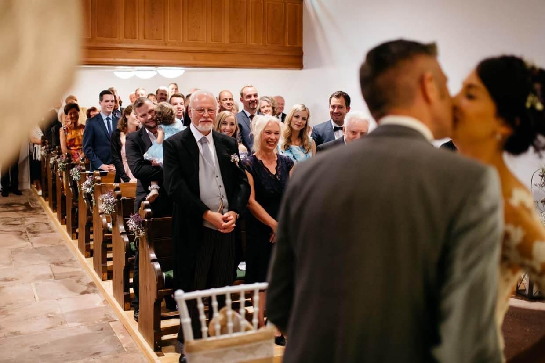Brautpaar küsst sich und emotionale Gäste