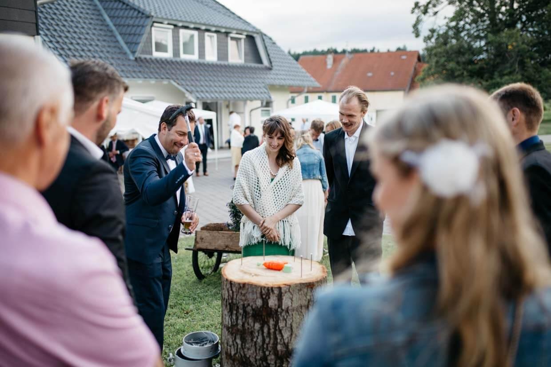 Hochzeitsgäste schlagen Nägel in Baumstamm