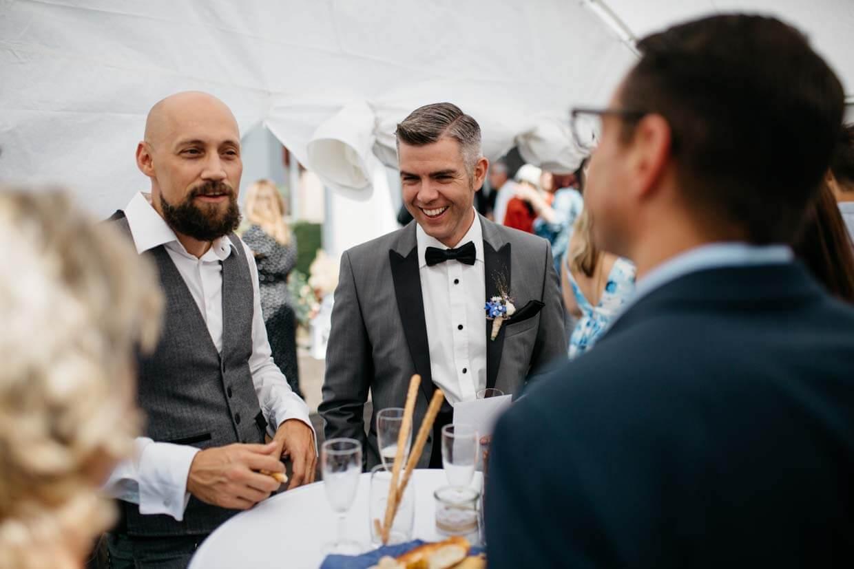 Bräutigam lacht mit Hochzeitsgästen