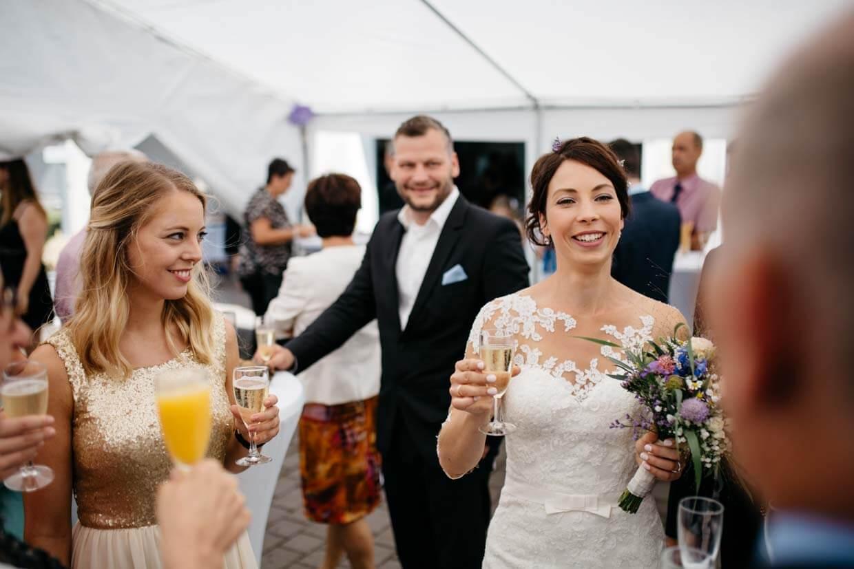 Braut stoßt mit Hochzeitsgästen an