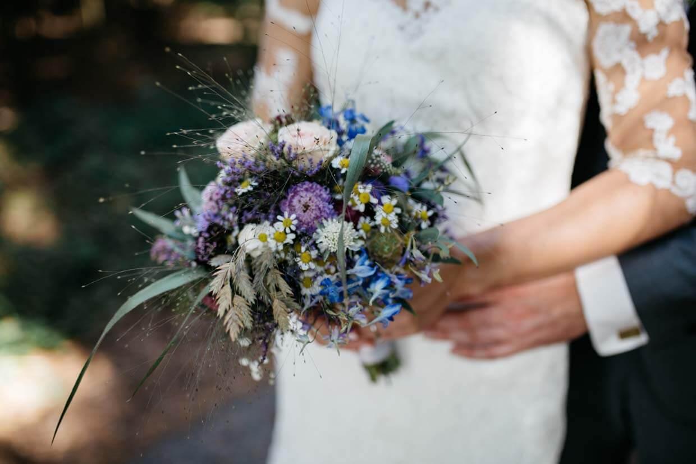 Braut und Bräutigam halten gemeinsam den Brautstrauß