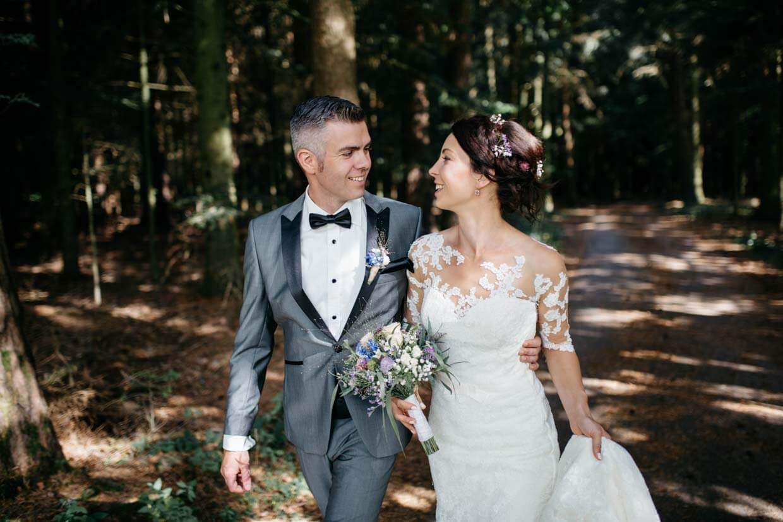 Brautpaar umarmt sich und geht im Wald spazieren