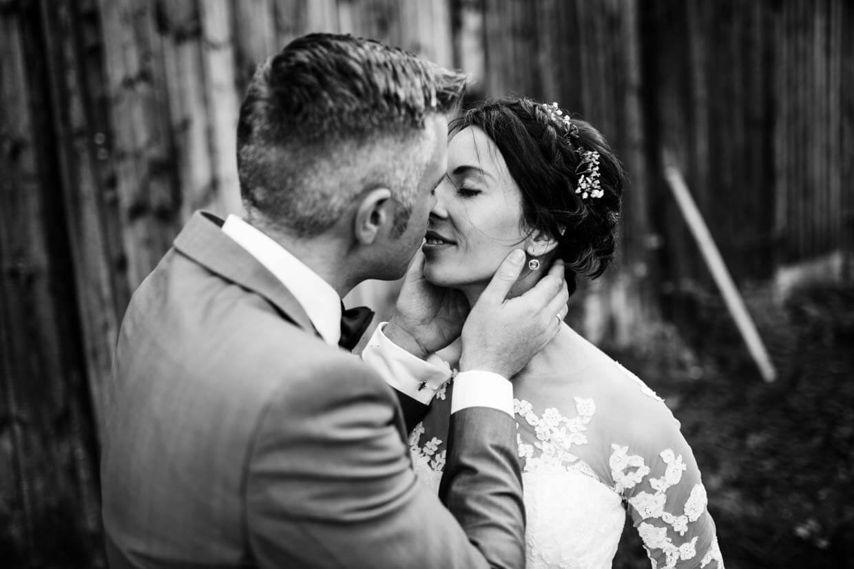 Bräutigam hält sanft den Kopf der Braut und küsst sie