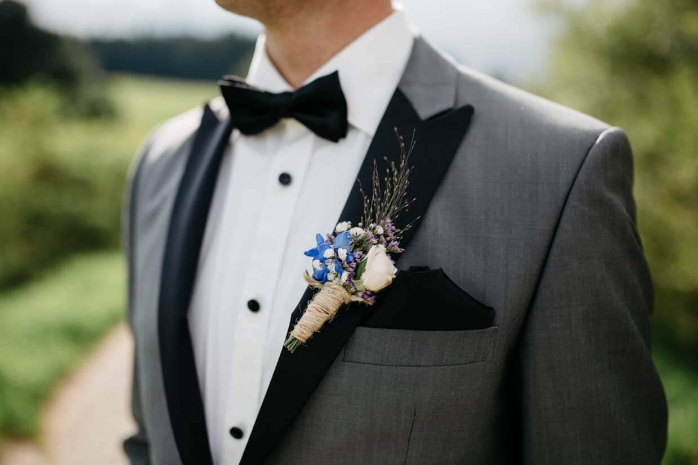 Detailaufnahme Anzug des Bräutigams mit Blumenanstecker und Fliege
