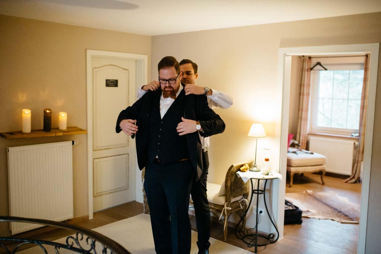 Trauzeuge hilft Bräutigam beim Anziehen des Sakko