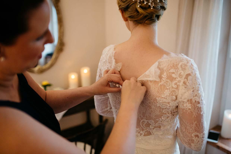 Braut beim Anziehen des Brautkleides