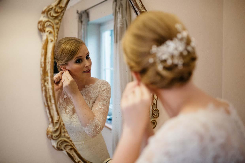 Braut steht vor dem Spiegel und zieht sich die Ohrringe an