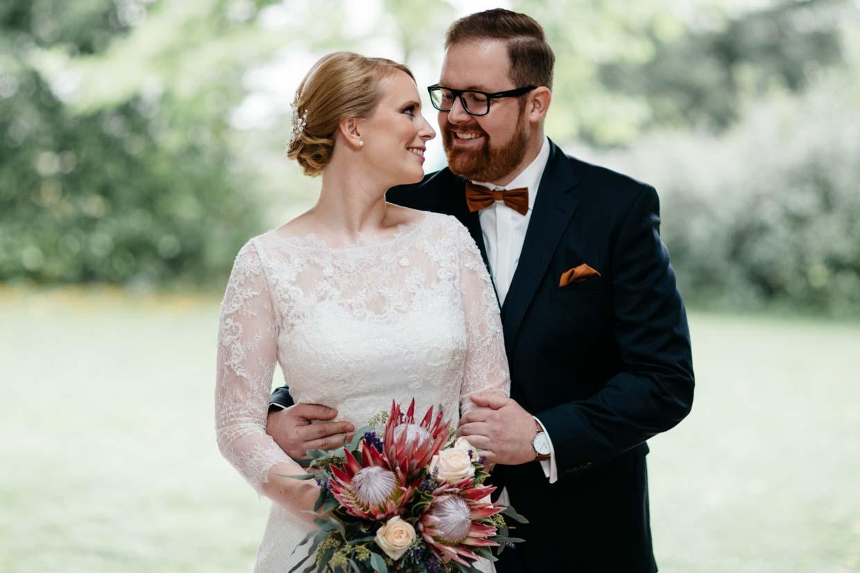 Bräutigam steht beim Brautpaarshooting hinter der Braut