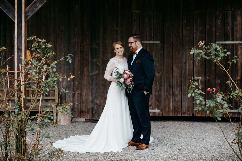 Brautpaar steht vor einer Scheune