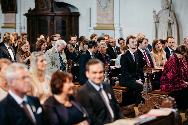 Hochzeitsgäste lachen in der Kirche
