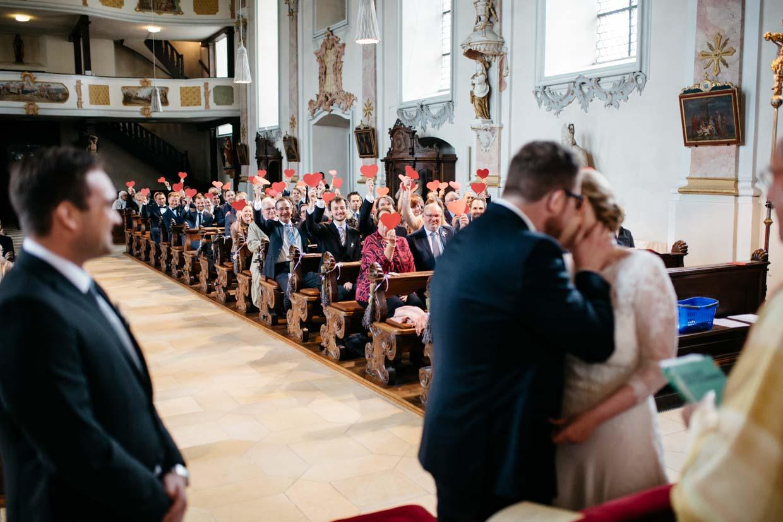 Brautpaar küsst sich bei der Trauung und Gäste halten Papierherzen hoch